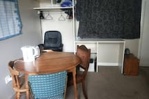 Dining area with 4 chairs, kettle and toaster. Closet to hang clothes and work desk.