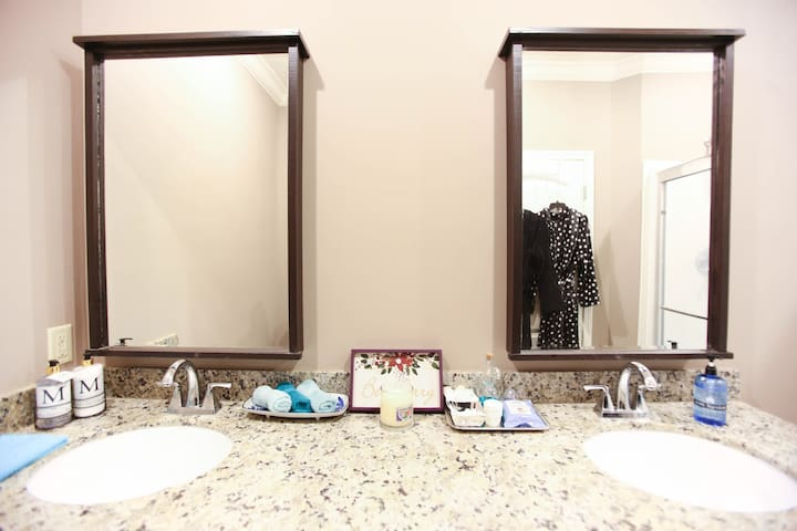 Double vanity with special touches such as candle, cotton swabs, mouthwash, hair dryer, soap, lotion, plush robes, bidet