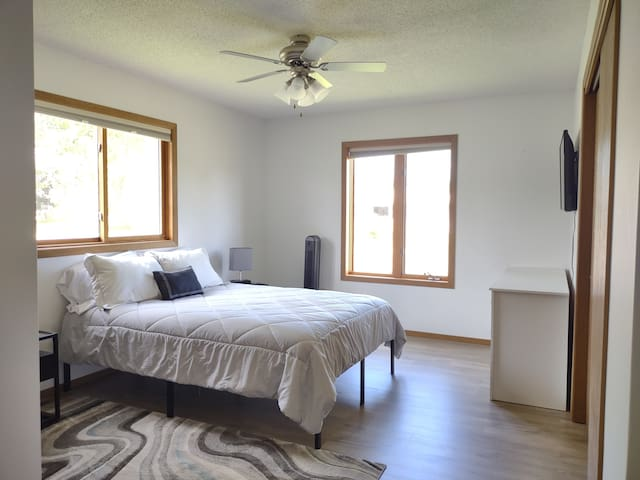 Master bedroom with comfortable queen bed and tv mounted against the east wall.