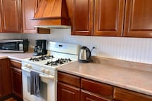 Full kitchen with microwave, gas stove and large oven- all plates, bakeware, pots and pans for your cooking pleasure.