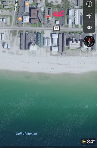 The pink arrow at the top of this picture is your condo! Just across a two-lane road and steps from the beach!