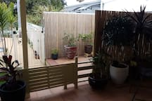 High fences and high screens for total privacy. We don't intrude either but you can call us any time you need something.  We don't mind to help. The Studio is right behind that cane screen. No one can see you.