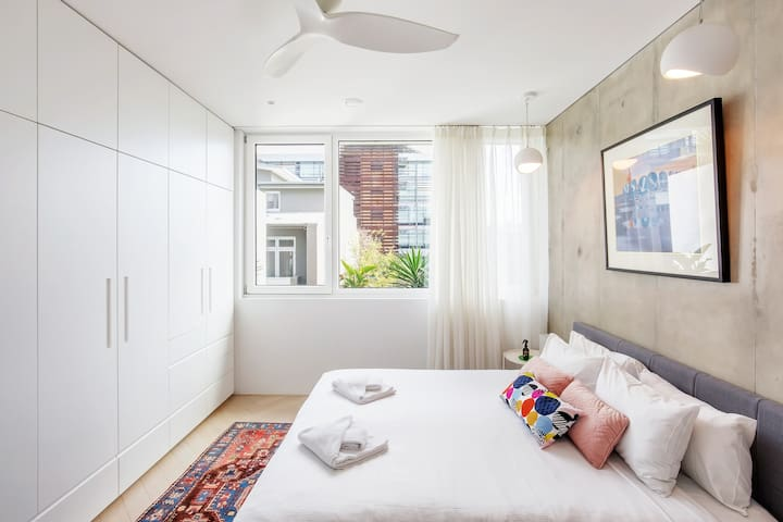 The bedroom features a queen bed, ample built-in storage space, and shut-out blinds. With triple-glazed doors and windows throughout, enjoy a good night's sleep in complete peace and quiet.