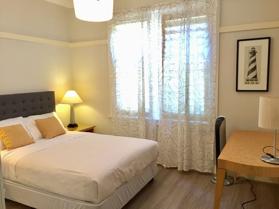 Bedroom 1 furnished with double bed, desk, reverse cycle air conditioner, fan and built wardrobe.