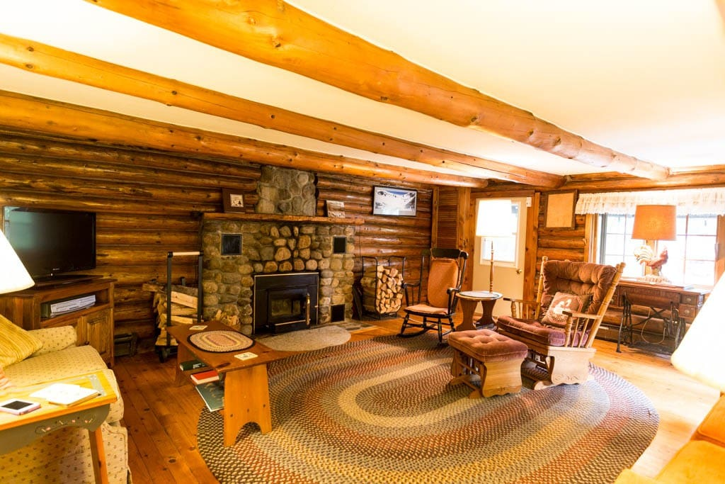 Living room with fireplace, two couches, sofa bed, originally the main cabin.
