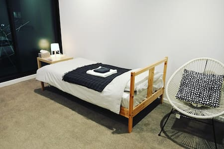 Bed in the living room (with wooden divider), CBD