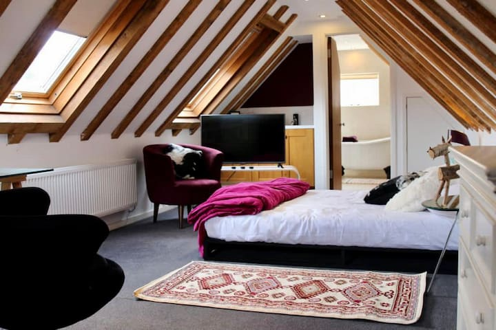 Large bedroom with seating and TV. Note this bedroom is spacious and open plan and provides access to the bathroom.
