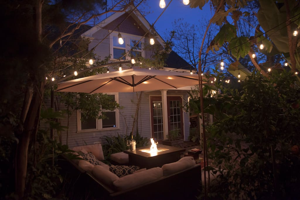 With some help from a fire pit and bistro lights, our courtyard transforms into this at night.
