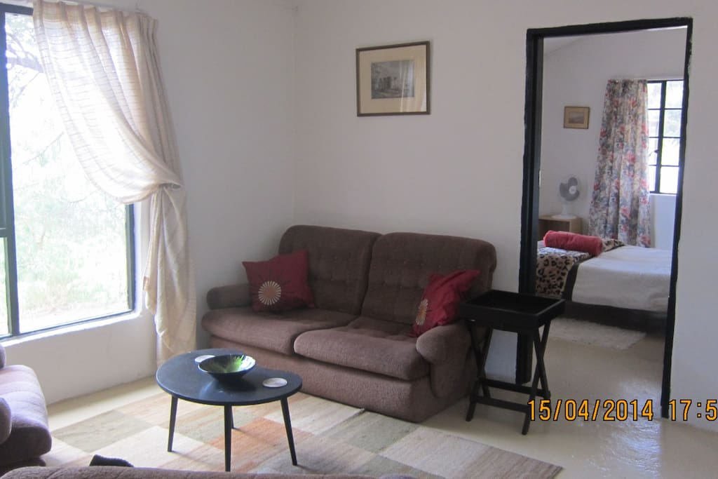 Comfy chairs and large windows in the living room and main bedroom - double bed.