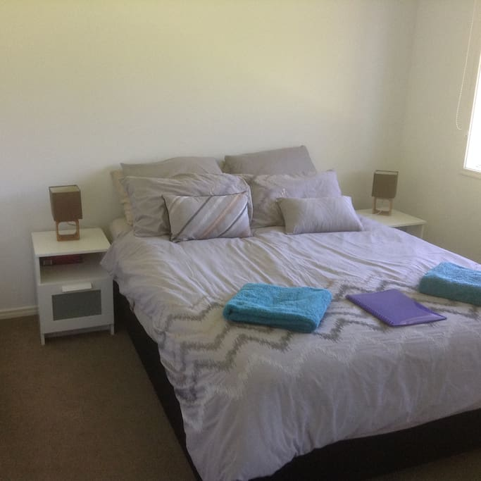 Queen bed in room with large cupboards