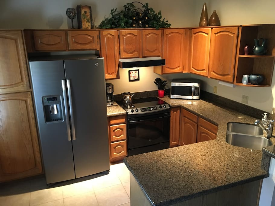 Fully equipped updated kitchen with a new stove, new refrigerator, granite  counter tops and tile flooring.