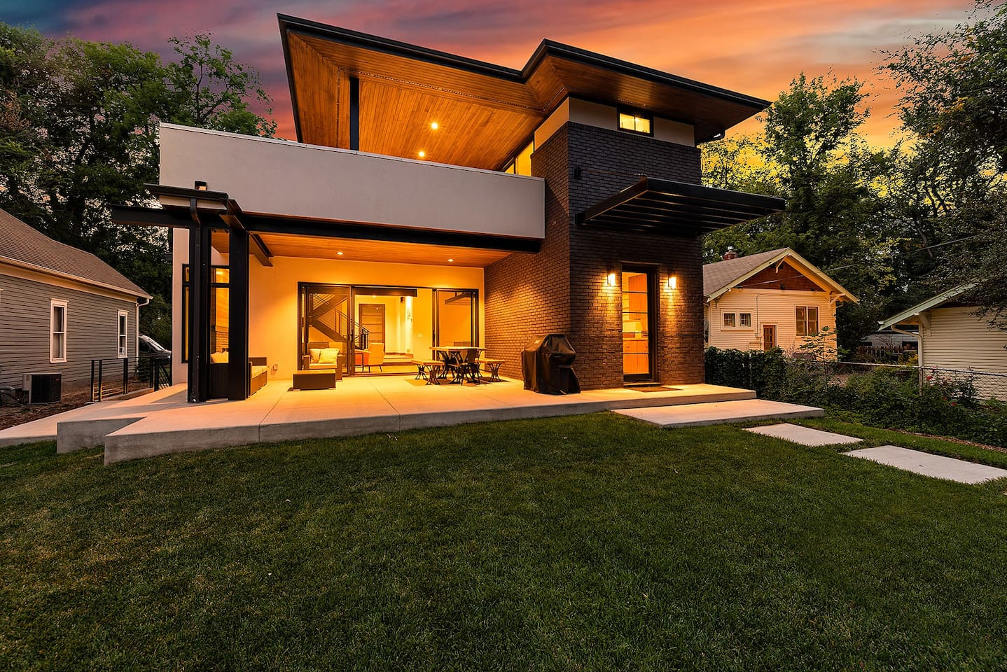 Sink in and relax in a flowing indoor-to-outdoor industrial design by an award-winning architect with floor-to-ceiling glass patio doors, fire pits, and colorful decor and art.