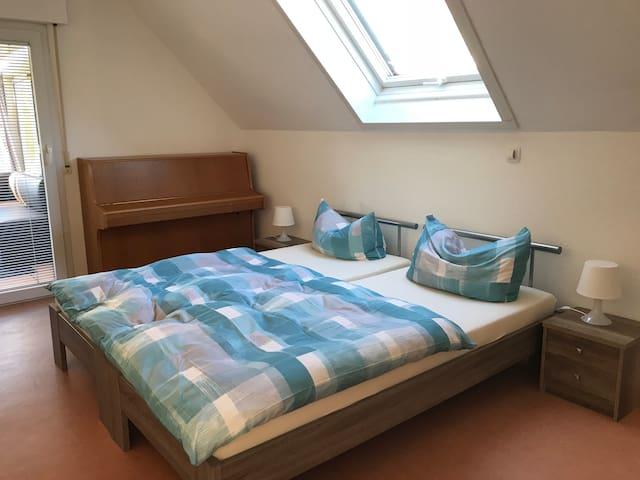 Schlafzimmer mit zwei Betten und Klavier, Zugang zum Balkon
