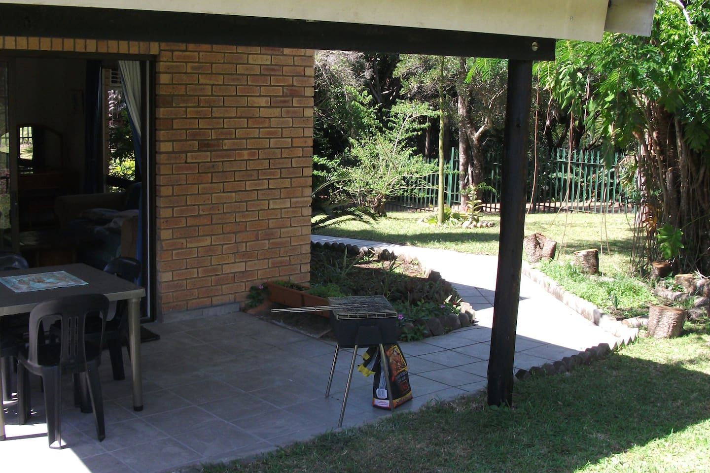 Entrance on Covered Patio with Furniture and BBQ Stand.