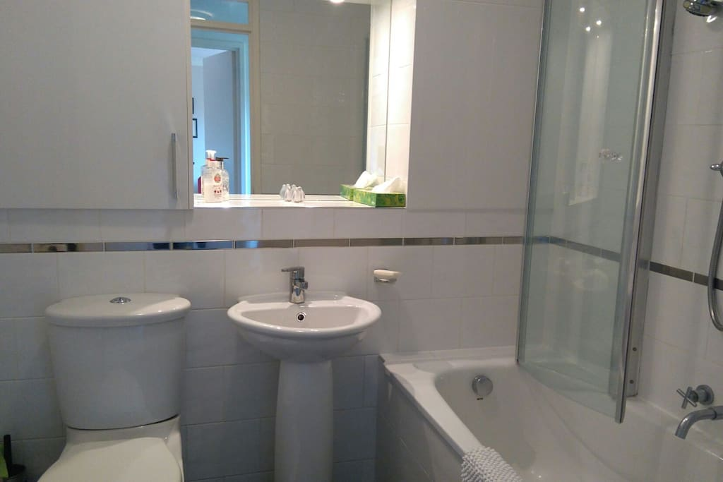 Shared bathroom with shower over the bath