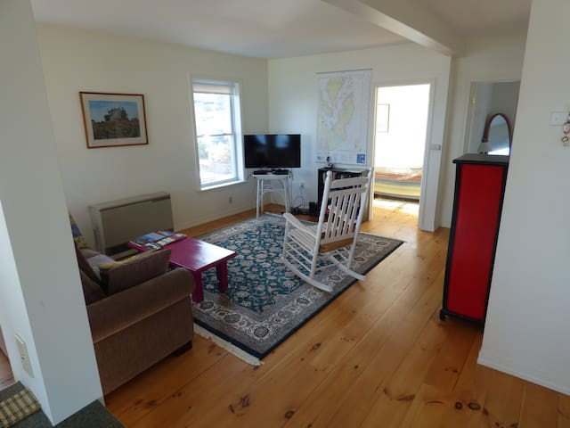 """Living room area with 40"""" HDTV, cable, DVD player."""