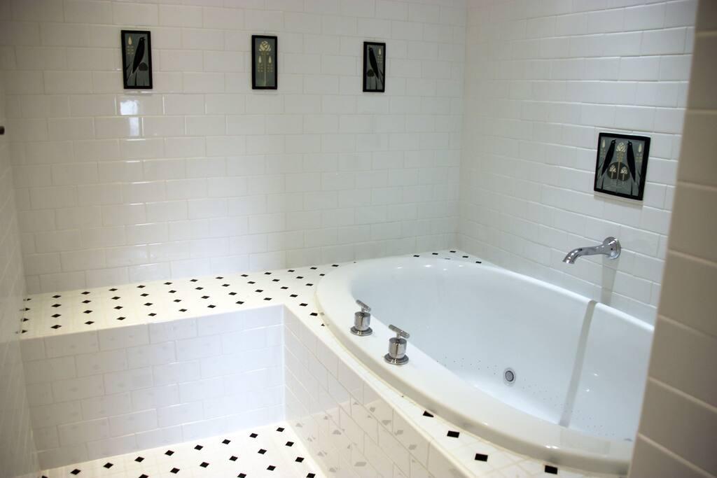 Private bath has a rain shower and Kohler spa tub