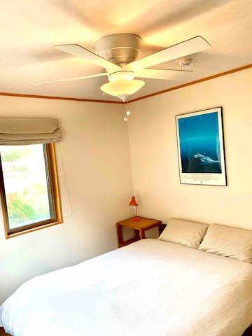 Double bed room with ceiling fan. 山側ゲストルームにはダブルベッド。2面採光で明るくて夏でも涼しげ。
