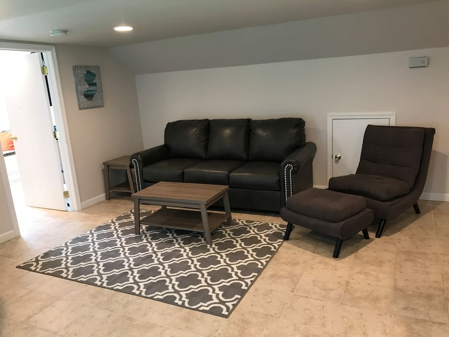 Living room with brand new leather queen size sleeper sofa with memory foam mattress.