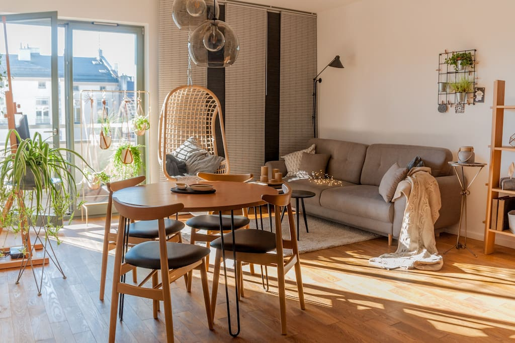 Spacious, bright and cosy living room with a working/dining space, TV, folding sofa, hanging chair and balcony access
