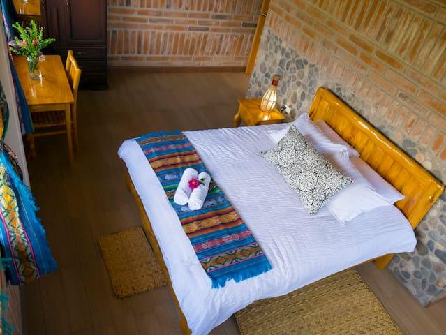 La habitación Master Yaku , cuenta con una cama rustica tamaño King Size sumamente amplia , el colchón es ortopédico y Las alomadas han sido elegidas para su descanso placentero . Ademas cuenta con una mesa y silla de madera rustica.