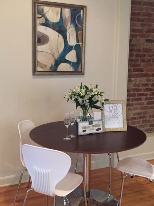 The new kitchen mid century dining table with fresh flowers and welcome note and chocolates