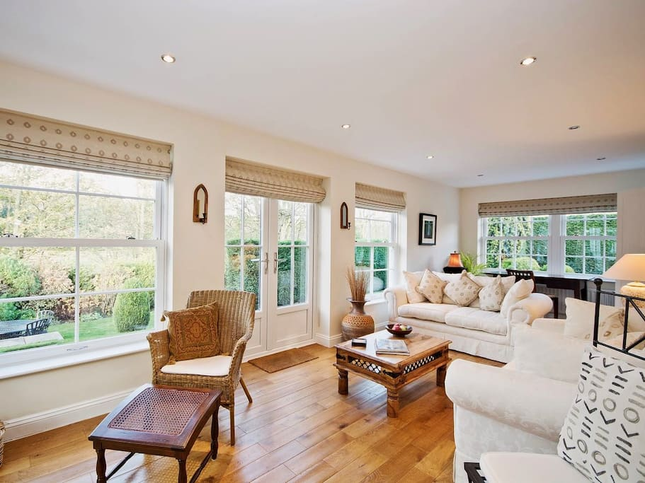 Light and airy orangery style lounge with french doors leading into large garden