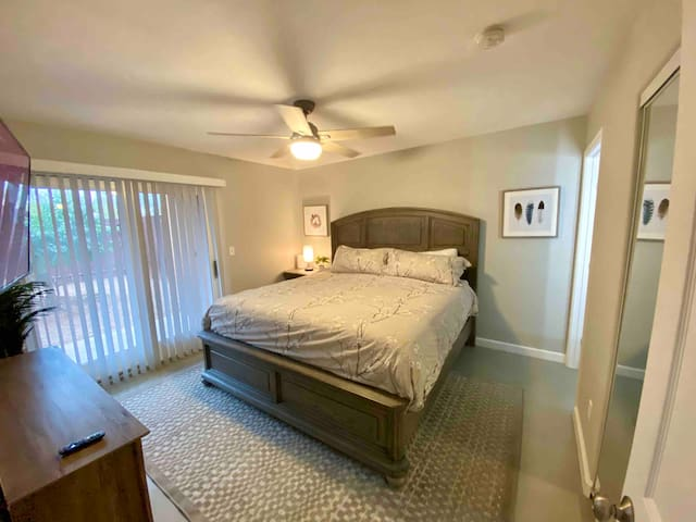 """Master bedroom with en-suite master bath. Brand new highly rated king memory foam mattress with luxury sheets and pillows. New 55"""" smart/roku tv that extents for better viewing and plugs in the lamp for easy access to charge your devices."""