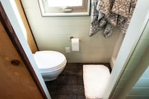 Wall mount toilet and shower with hot water on demand (that means long, hot showers).