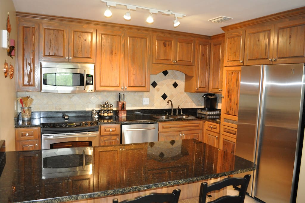 Custom Kitchen with high end appliances. Keureg and Coffee pot.