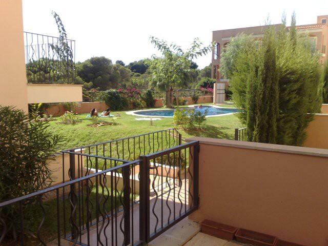 Bajo con jardín y piscina.