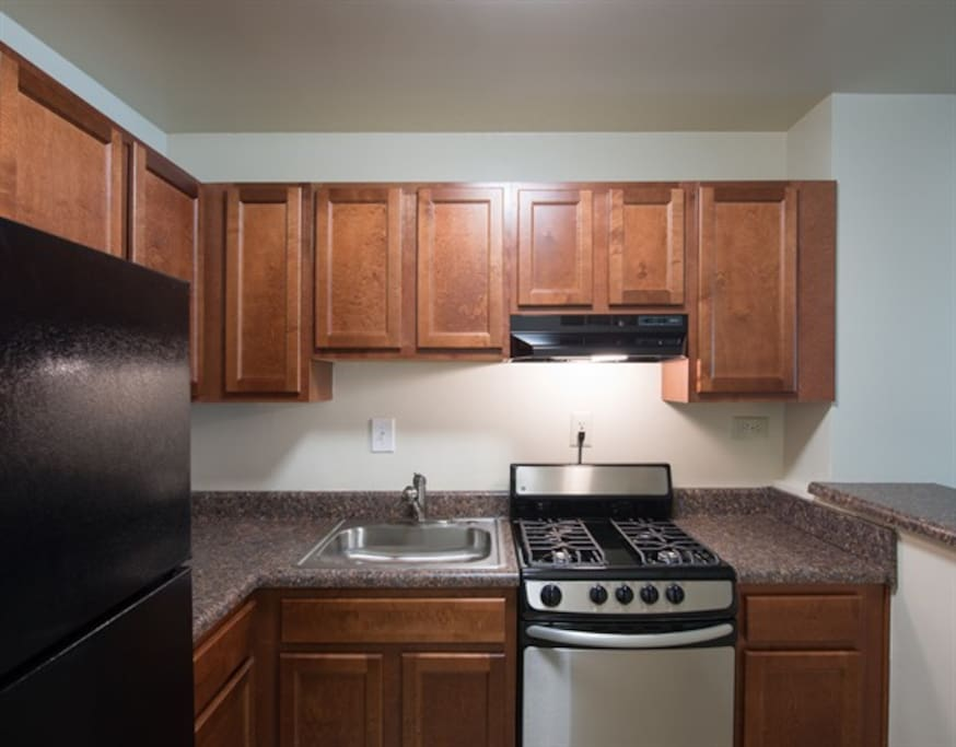 View from the entrance to a spacious full kitchen. The appliances have recently been renovated and will be cleaned and sanitized prior to guest arrival. Kitchenware provided. Included: Full refrigerator with freezer, gas stove and oven and bar with stools. (Updated pictures will be uploaded momentarily).
