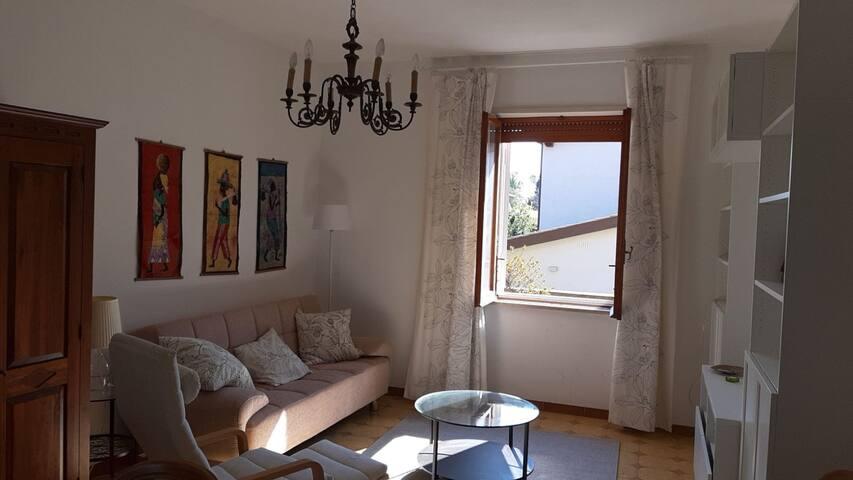 Salone spazioso, con divano letto, poltrona, televisione, tavolo con sedie e mobile libreria.