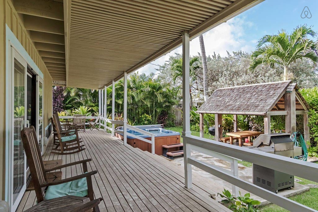 comfy rocking chairs and a hammock that overlook the tropical landscaped garden