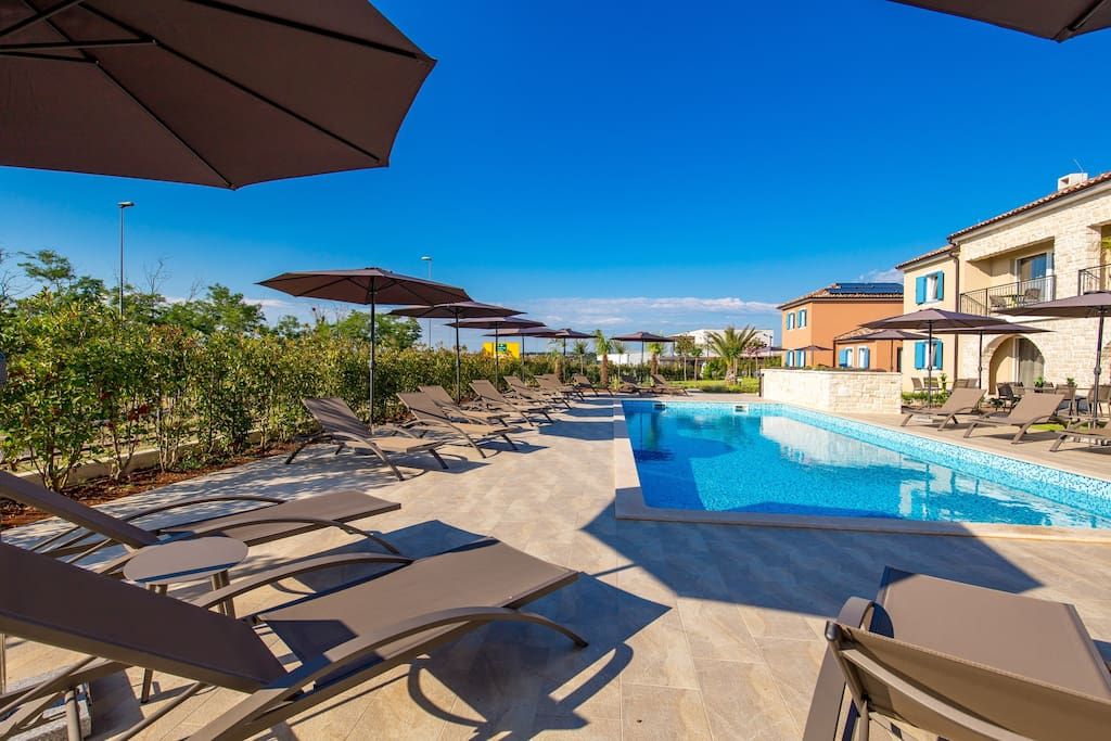 Pool with deck chairs and umbrellas
