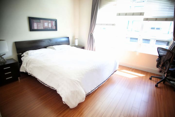 """Master bedroom with King bed. It's equipped with  desk, Herman Miller chair, and a 55"""" TV"""