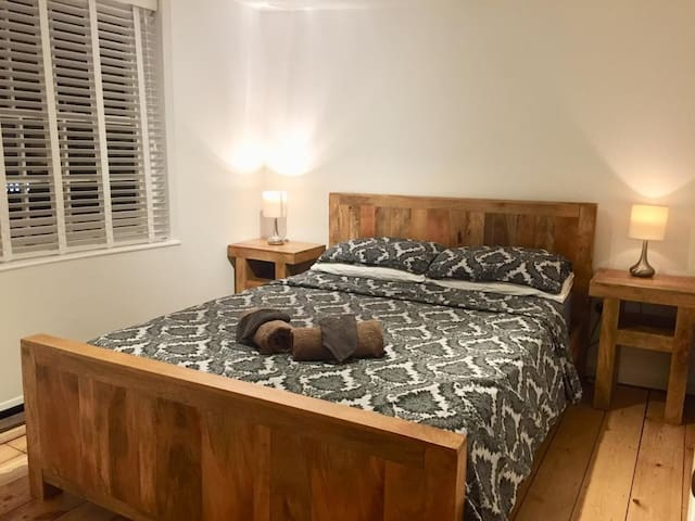 king size solid mango wood bed with matching bedside tables and touch dimming lamps, a fitted wardrobe and Usb port for charging.