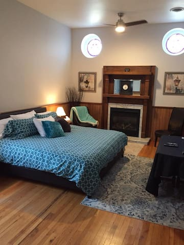 The King Suite with king bed, gas fireplace, stained glass windows,  smart TV, wainscotting and ensuite bathroom.