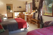 Studio set up with Queen bed and two single beds.