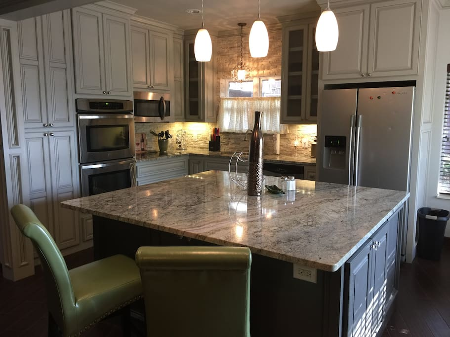 Kitchen equipped with dishes, cookware, double oven, microwave & ceramic cooktop