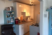 Full kitchen with ice maker, coffeemaker, stove and fridge