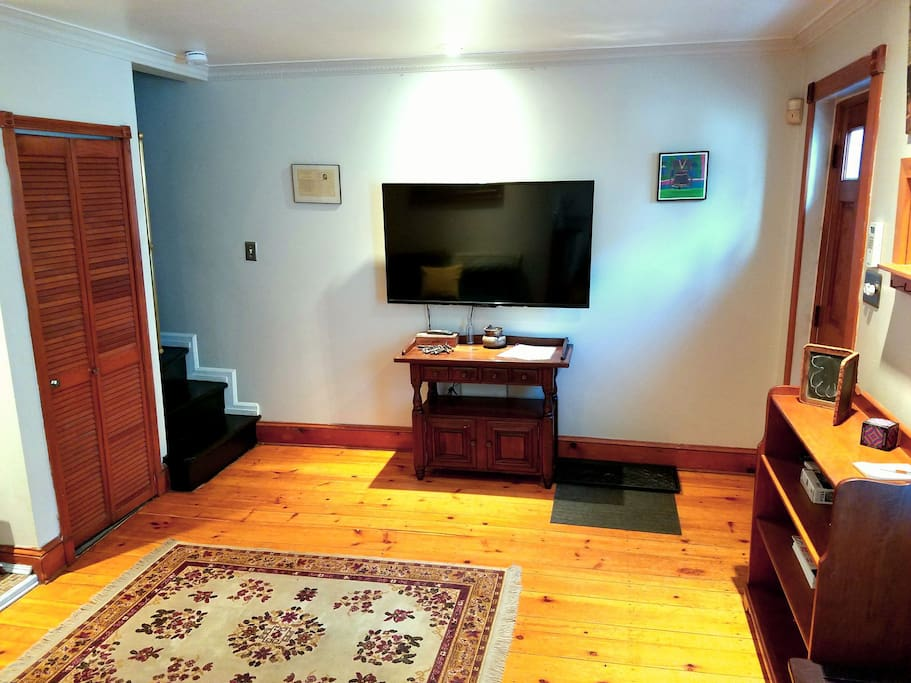 """Living room with 55"""" TV, love-seat that pulls out to bed, historic wide-plank wood floors, gas fireplace"""