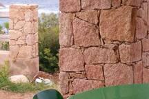 Scorcio di rocce rosse che si sposano con gli scogli di fronte