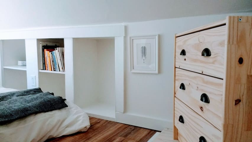 Bedroom has storage nooks for clothing and travel bags on both sides and a small dresser.