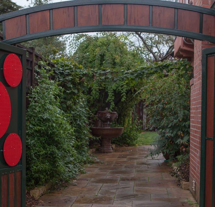 Secret garden entry through driveway gate.