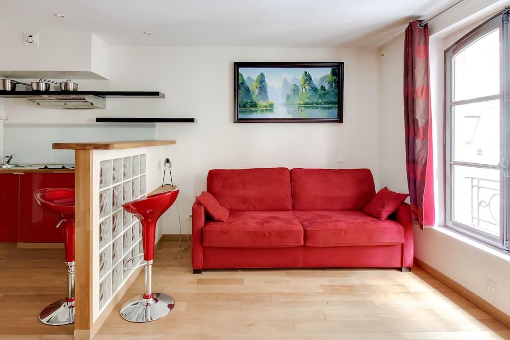 Salon avec canapé, petit bureau et cuisine américaine