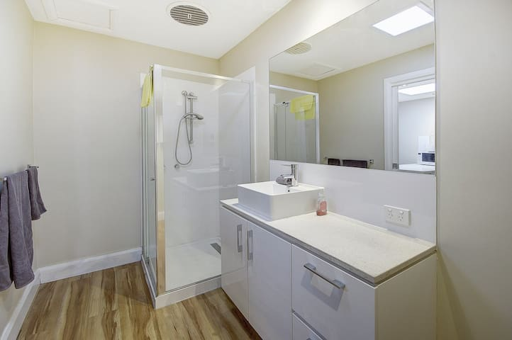 The bathroom - practical and easy to maintain, a vanity basin & mirror a step in shower and toilet