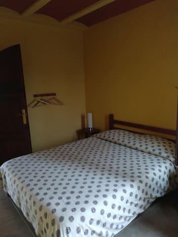 Habitación doble.  Armario totalmente abierto, silla y mesas de noche .  Ventana exterior con mosquitera .