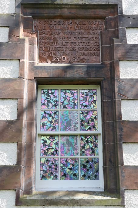 The amazing historical plaque on the front of the house with the stained glass window underneath.