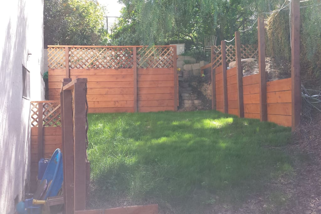 Private backyard with patio for BBQ, grass for playing, and shade for hot days.